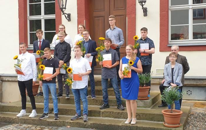 Gruppenbild der Absolventen der SABEL Schule Saalfeld mit Zeugnis und Sonnenblume